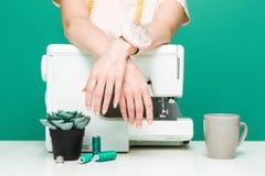 Шить мастерская Конец-вверх рук белошвейки на покрашенной предпосылке стоковая фотография