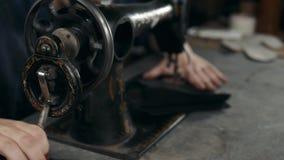 Шить процесс фабрики продукции кожаных ботинок кладет пояс в мешки Руки ` s человека за шить Кожаная мастерская handmade сток-видео