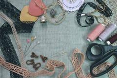 Шить состав таблицы сцены плоский положенный Потоки, шнурок, штыри, ножницы, лента, вьюрок, ткань Ткань белья пастельных цветов стоковая фотография rf