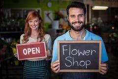 Шифер удерживания человека с знаком цветочного магазина и шильдиком удерживания женщины открытым Стоковые Фото