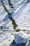 Шишка снега свернула вниз холм и тропа появилась с зеленой травой в парке на солнечный весенний день ` S детей стоковое фото rf