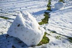 Шишка снега свернула вниз холм и тропа появилась с зеленой травой в парке на солнечный весенний день ` S детей стоковая фотография