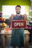 Шильдик мужского удерживания флориста открытый на его цветочном магазине Стоковое Изображение RF