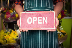 Шильдик мужского удерживания флориста открытый на его цветочном магазине Стоковое фото RF