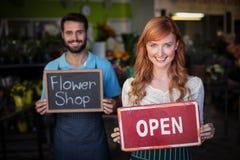 Шильдик удерживания женщины открытые и удерживание человека намечают с знаком цветочного магазина Стоковые Изображения