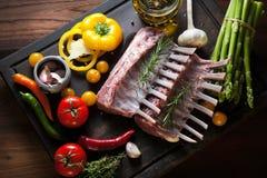 Шкаф овечки, сырого мяса с косточкой на деревенском кухонном столе на деревянной предпосылке стоковые изображения rf