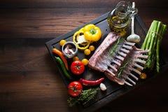 Шкаф овечки, сырого мяса с косточкой на деревенском кухонном столе на деревянной предпосылке стоковые изображения