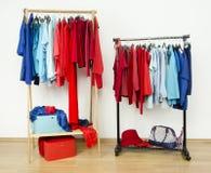 Шкаф при красные и голубые одежды вися на славно аранжированном шкафе стоковая фотография rf