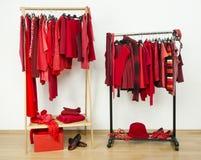 Шкаф при красные одежды вися на славно аранжированном шкафе стоковые изображения rf