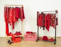 Шкаф при красные одежды вися на славно аранжированном шкафе стоковое изображение rf