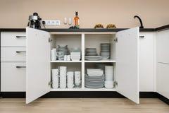 Шкаф хранения посуды с плитами и чашками внутрь стоковая фотография