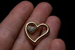 Шкентель старого золота в форме сердца, с меньшим сердцем cristal внутренности, на подарке дня ` s валентинки в руке на черном b Стоковое Фото