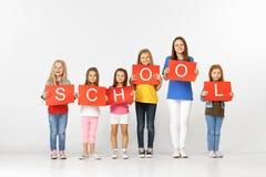 школа Группа в составе дети с Красными знаменами изолированными в белизне стоковые изображения