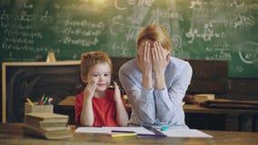 Школа семьи Родители уча детям частным урокам Мальчик и женщина покрывая их стороны с ладонями в классе школы видеоматериал