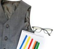 Школа установила с жилетом, карандашами, ручками войлок-подсказки, и стеклами на белой предпосылке E E концепция образования для стоковые изображения rf