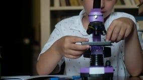 Школьник в белой рубашке смотрит в фиолетовый микроскоп и записывает в сток-видео