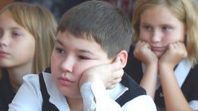 Школьник в классе сидя на столе акции видеоматериалы