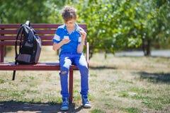 Школьник играя с обтекателем втулки и smartphone непоседы после класса стоковое изображение rf