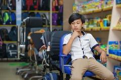 Школьник мальчика портрета портрета азиат рюкзака магазина покупки сидит одно поставляет студента начальной школы стула офиса наж стоковое фото rf