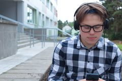 Школьник подростка мальчика или студент в рубашке, улыбки в стеклах, слушают к музыке на телефоне Стоковые Изображения RF