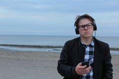 Школьник подростка мальчика или студент в рубашке, улыбки в стеклах, слушают к музыке на телефоне стоковая фотография rf