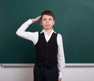 Школьник показывать воинский салют, портрет около зеленой пустой предпосылки доски, одел в классическом костюме, одном зрачке, ed Стоковые Фотографии RF