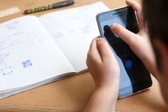 Школьник при smartphone делая домашнюю работу дома Стоковое Изображение