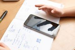 Школьник при smartphone делая домашнюю работу дома Стоковые Изображения RF