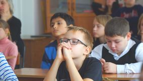 Школьник со стеклами в классе сидя на столе видеоматериал
