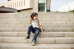 Школьник с животиком на его плечах и крышке сидит на шагах в город и уныло думает о что-то стоковое фото