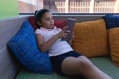 Школьница изучая на цифровом планшете пока распологающ на кресло в школьной библиотеке стоковое фото rf