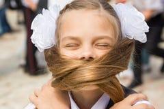 Школьница на празднике 1-ого сентября покрыла ее сторону с ее длинными волосами стоковые фото