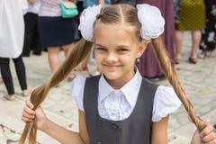 Школьница на фестивале 1-ого сентября держит ее длинные волосы в ее руках стоковое фото