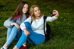 Школьница 2 подруг Лето в парке в природе Сидите на траве, рюкзаках В его руках держит smartphone Стоковое Фото