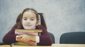 Школьница сидит на таблице Во время этого танца, она смотрит камеру Обнимать стог книг положило видеоматериал