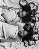 Школьницы в розовых пижамах спят на красочных подушках, взгляд сверху Девушки на белой и розовой предпосылке простынь стоковые изображения