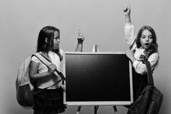 Школьницы рядом с доской на розовой предпосылке Девушки с удивленными сторонами держат пальцы вверх имея идею Носить детей Стоковое Изображение RF