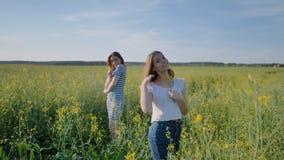 5 школьниц представляя с цветками в поле рапса сток-видео