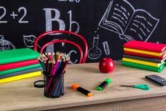 Школьные принадлежности и аксессуары Книги, ручки войлок-подсказки, лупа, красное яблоко etc и доска на стоковые изображения rf