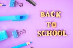 Школьные принадлежности на фиолетовой предпосылке готовой для вашего дизайна Плоское положение Взгляд сверху Стоковое фото RF