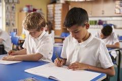 2 школьника работая в классе начальной школы, конец вверх стоковые изображения