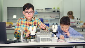 Школьники делая эксперименты по науки в лаборатории школы сток-видео