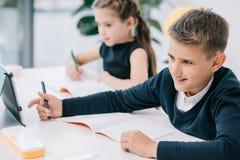 Школьники писать в пустых ученических книгах пока изучающ на столе Стоковые Фотографии RF