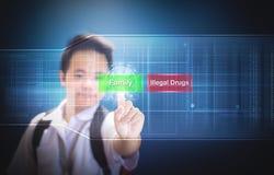 Школьник выбирая семью кнопки вместо нелегальных наркотиков используя технологию hologram виртуального экрана Семья или лекарства Стоковая Фотография RF