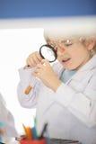 Школьник в пальто лаборатории держа лупу и смотря образец в трубке стоковые фотографии rf