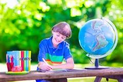 Школьник делая домашнюю работу в школьном дворе Стоковое фото RF