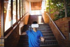 Школьник используя шлемофон виртуальной реальности на лестнице Стоковая Фотография
