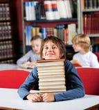 Школьник отдыхая Chin на стоге книг Стоковая Фотография
