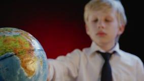 Школьник поворачивает глобус акции видеоматериалы