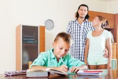 Школьник подростка делая домашнюю работу против родителей Стоковые Изображения RF